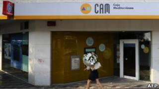 Mulher caminha diante do banco Caja Mediterráneo em Madrid.