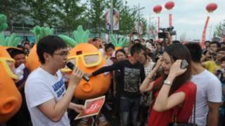 Pang Kun e amigos vestidos de cenoura diante de sua noiva, Zhang Xinyu, a quem ele pediu em casamento (Qurky News China / Rex Features)