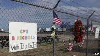 Цветы и флаги США на заборе военной базы