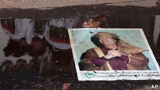 Cartaz com rosto de Khadafi em poça em frente à Embaixada Líbia em Brasília (Foto: AP)