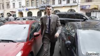 Прохоров идет между двумя машинами