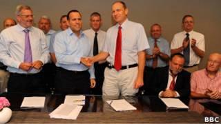 Представители минфина Израиля и профсоюзов медработников пожимают руки после подписания соглашения