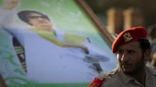 جندي أمام جدارية للقذافي في سرت