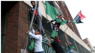 محتجون يرفعون علم الثورة الليبية على السفارة في هاراري