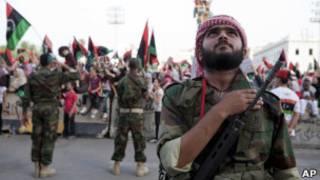 Combatente rebelde põe a mão sobre o coração ao ouvir o novo hino nacional no centro de Trípoli