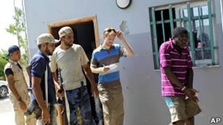 Ливийские повстанцы и иностранный журналист смотрят на темнокожего африканца, задержанного по подозрению в наемничестве (28 августа 2011 года)