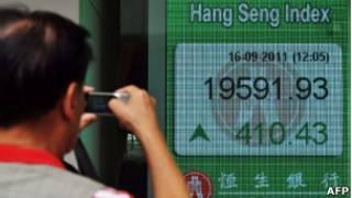 Homem tira foto de letreiro com cotações da Bolsa de Seul