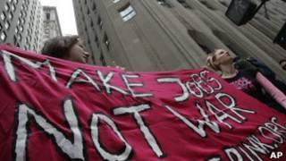 """متظاهرون في وول ستريت يحملون لافتة كتب عليها """"اخلقوا وظائف وليس حروبا"""""""