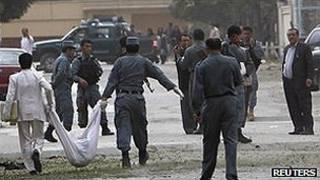 Policía afgana carga un cuerpo tras un atentado en Kabul