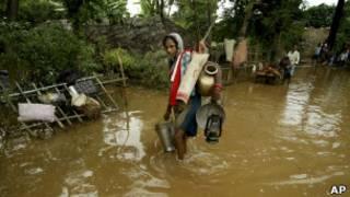 Женщина идёт по затопленной дороге