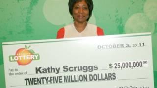 Kathy Scruggs posa com réplica gigante de cheque da loteria da Geórgia