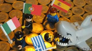 Иллюстрация: игрушечная акула ест человечков с флагами Греции, Испании, Италии и Португалии