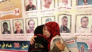 Palestinas se abraçam diante de fotos de prisioneiros que podem ser soltos por Israel