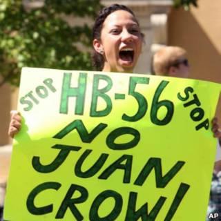 Mulher protesta contra lei de imigração do Alabama.