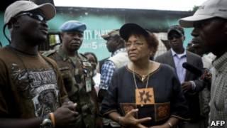 Presidente Sirleaf (centro) conversa com partidários neste sábado (AFP)