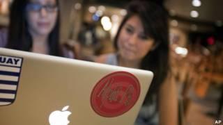 Dos jóvenes ven la pantalla de un laptop