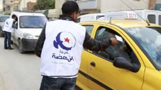 ناشط في حركة النهضة يوزع ملصقات انتخابية
