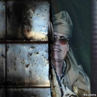 Banner semidestruído de Khadafi visto em prédio em Sirte (Reuters)