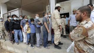 طابور لليبيين بانتظار إلقاء نظرة على جثة القذافي وابنه ووزير دفاعه