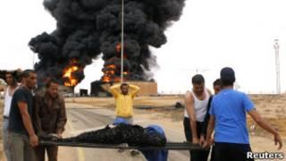 Жители несут обуглившееся при взрыве тело