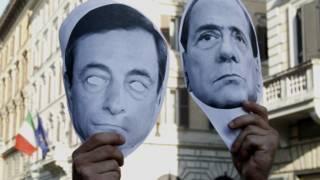 Mặt nạ hình ông Berlusconi (phải) bị trưng ra trong biểu tình phản đối trước Ngân hàng Quốc gia Ý