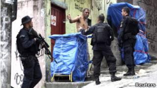 Policiais falam com morador da Rocinha ao subir o morro no domingo (Foto: Reuters)