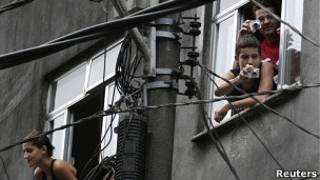 Moradores da Rocinha tiram foto durante ocupação da favela pela polícia (Foto: Reuters)