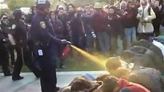 مامور پلیس دانشگاه کالیفرنیا که اسپری گاز فلفل را به سر و صورت دانشجویانی میزند که بیحرکت روی زمین نشستهاند