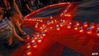 Свечи на алой ленте в память о жертвах СПИДа
