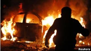 Manifestante ateia fogo a carro durante a madruga em Alexandria (Foto: Reuters)