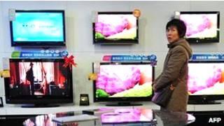 زنی در یک فروشگاه تلویزیون در چین