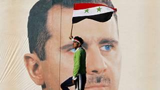 Một ngơời biểu tình đi ngang qua chân dung Tổng thống Syria Assad