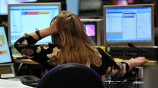 Una mujer se agarra la cabeza frente a su computador