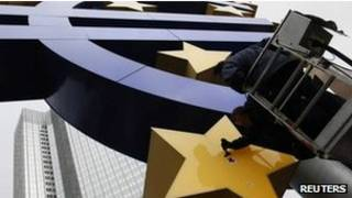 Homem retoca símbolo do Euro em Frankfurt. Reuters