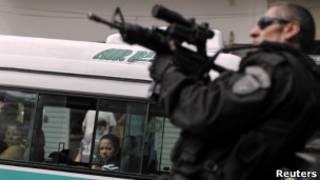 Policial é observado por passageiros de ônibus enquanto mira sua arma durante uma operação contra traficantes na favela da Rocinha, no Rio, em abril de 2011 (Reuters)