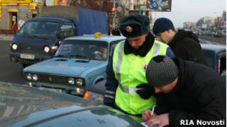 Российский полицейский оформляет протокол после ДТП в Омске