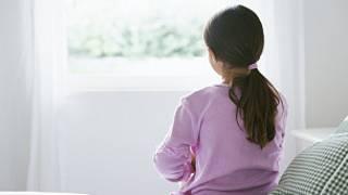 niña mira a través de su ventana