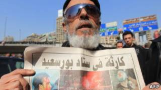 مصري يحمل صحيفة يشير عنوانها إلى احداث بورسعيد