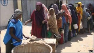صوماليون يتلقون وجبات غذائية في معسكر للنازحين في مقديشو