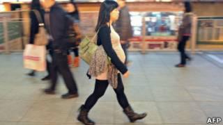 Беременная женщина на улице Гонконга