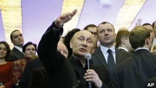 Putin saúda correligionários na sede de seu comitê eleitoral em Krasonoyarsk, na Rússia (AP)