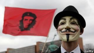 Ativista mascarado em protesto em Berlim. | Foto: Getty