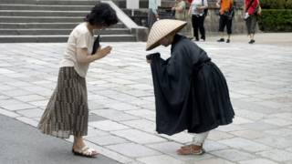 A Japanese woman bows in greeting to a monk.