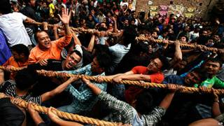 A crowd of Nepalese men pulling on ropes