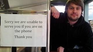 Даррен Грум на фоне объявления об отказе обслуживать клиентов, разговаривающих по телефону