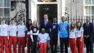 英國首相卡梅倫在唐寧街10號門前與奧運志願者代表合影