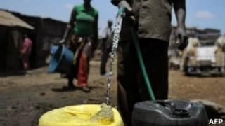 Человек заливает воду из шланга в пластмассовые баки