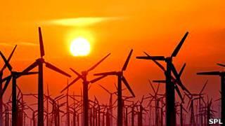 Un campo de turbinas de viento en la puesta del Sol