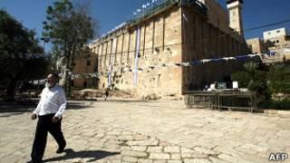 Homem passa em frente a mesquita em Hebron, na Cisjordânia; cidade foi decorada pela primeira vez em 46 anos para celebrar aniversario de Israel (AFP)