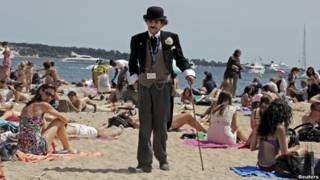 A man dressed as Charlie Chaplin walks on the beach